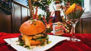 Image of a half-pound local burger and a bottle of Shiner Holiday cheer beer